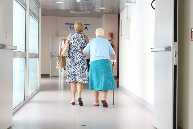 nursing home covid-19 long-term care facility Adult Woman Walking with Her Senior Mother in the Hospital
