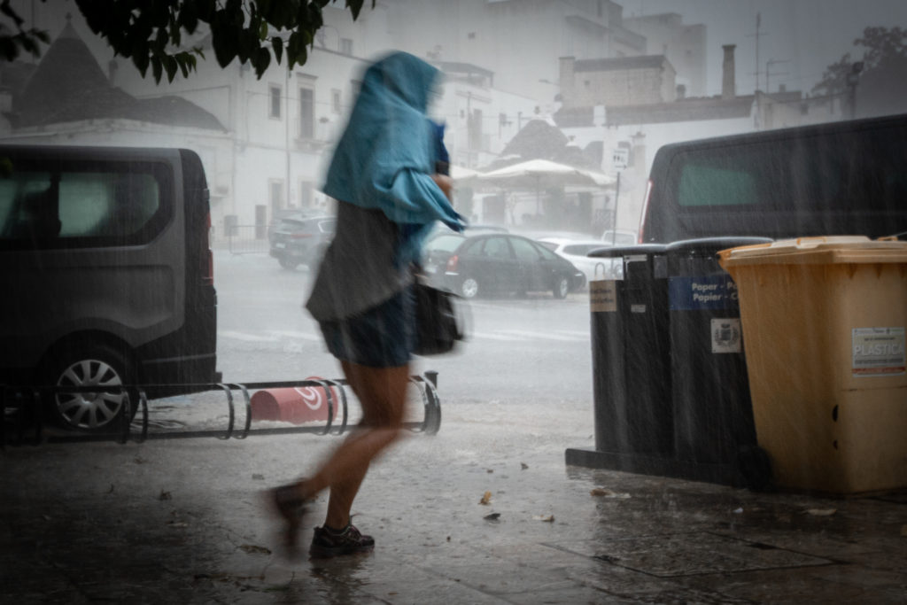 severe weather preparedness wet woman without umbrella runnung during thunderstorm in alberobello puglia italy
