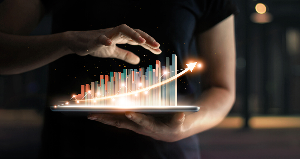 Businessman holding tablet and showing a growing virtual hologram of statistics, graph and chart with arrow up on dark background. Stock market. Business growth, planing and strategy concept