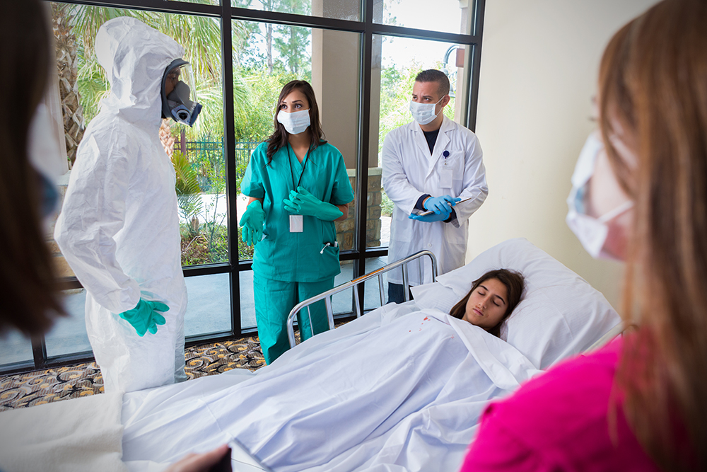 Hospital staff wearing masks and protective gear around infected patient