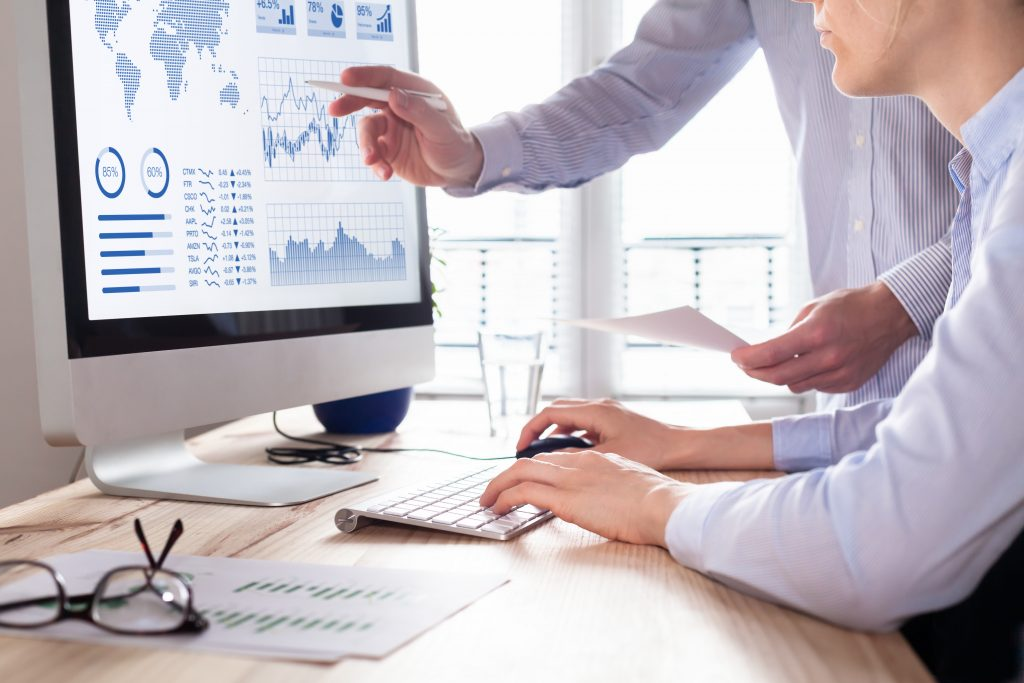 Two people analyzing stock market investment strategy with key performance indicator on financial dashboard and business intelligence on computer
