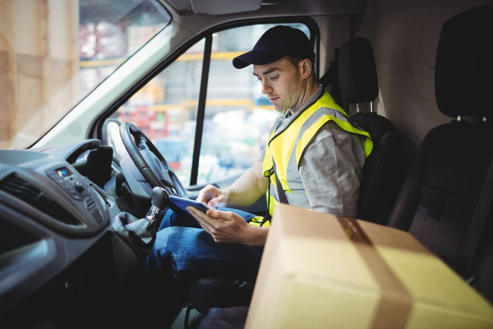 Delivery driver using tablet in van with parcels on seat