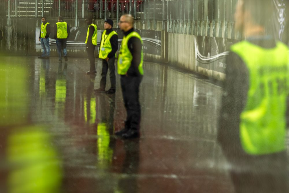 Security employees standing in a line at a stadium on a sporting event at night.