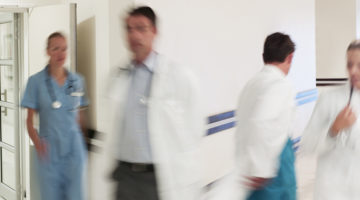 Doctors in hospital corridor practicing clinical collaboration