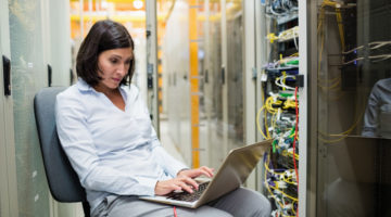 Female information technology professional fixing an IT issue in a server room
